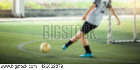 Blurry Image Of Soccer Player Running To Kicking With Blurry Ball On Green Artificial Turf.