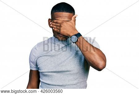 Young black man wearing casual t shirt covering eyes with hand, looking serious and sad. sightless, hiding and rejection concept