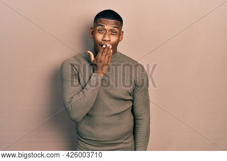 Young black man wearing casual turtleneck sweater bored yawning tired covering mouth with hand. restless and sleepiness.