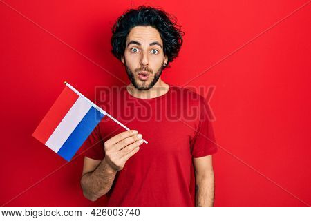 Handsome hispanic man holding netherlands flag scared and amazed with open mouth for surprise, disbelief face