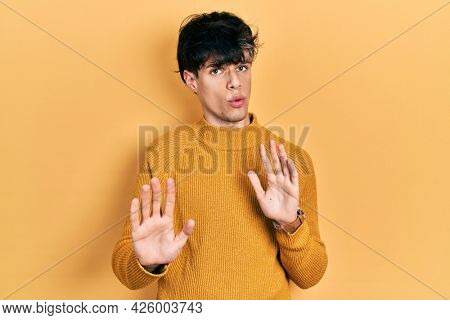 Handsome hipster young man wearing casual yellow sweater moving away hands palms showing refusal and denial with afraid and disgusting expression. stop and forbidden.
