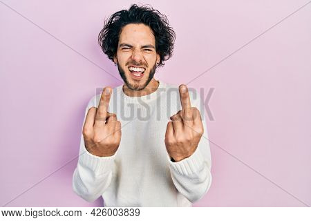 Handsome hispanic man wearing casual white sweater showing middle finger doing  bad expression, provocation and rude attitude. screaming excited