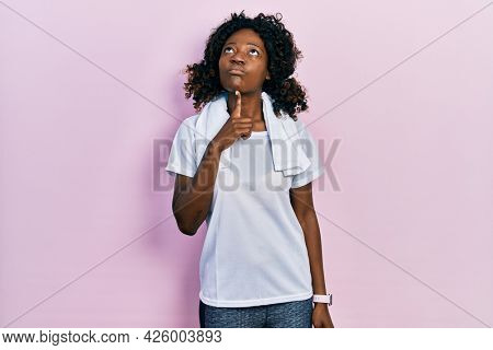 Young african american woman wearing sportswear and towel thinking concentrated about doubt with finger on chin and looking up wondering