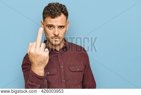 Young hispanic man wearing casual clothes showing middle finger, impolite and rude fuck off expression