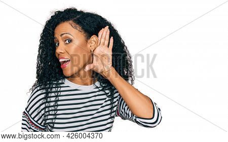 Middle age african american woman wearing casual clothes smiling with hand over ear listening an hearing to rumor or gossip. deafness concept.