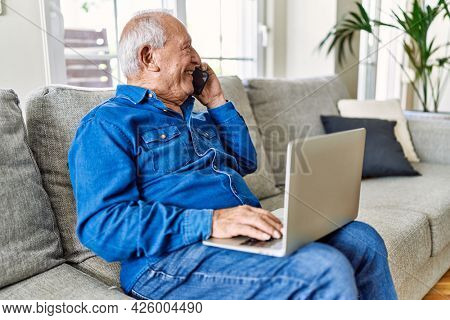 Senior man with grey hair sitting on the sofa at the living room of his house using computer laptop and speaking on the phone