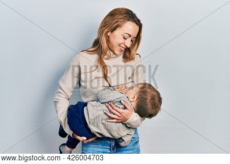 Young caucasian woman holding and hugging her son breastfeeding him, maternity lactation