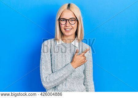 Beautiful blonde woman wearing glasses cheerful with a smile of face pointing with hand and finger up to the side with happy and natural expression on face