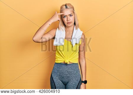 Beautiful blonde sports woman wearing workout outfit pointing unhappy to pimple on forehead, ugly infection of blackhead. acne and skin problem