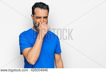Middle aged man with beard wearing casual blue t shirt smelling something stinky and disgusting, intolerable smell, holding breath with fingers on nose. bad smell
