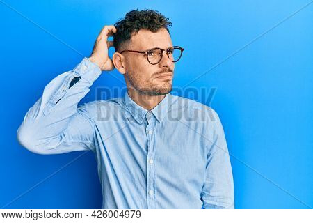 Young hispanic man wearing casual clothes and glasses confuse and wondering about question. uncertain with doubt, thinking with hand on head. pensive concept.