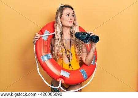 Beautiful young blonde woman wearing bikini and holding lifeguard float and binoculars smiling looking to the side and staring away thinking.