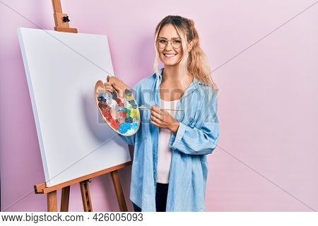Beautiful young blonde woman standing drawing with palette by painter easel stand smiling with a happy and cool smile on face. showing teeth.