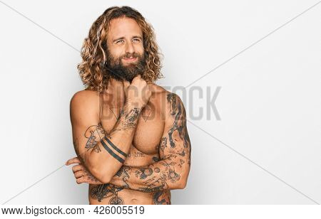 Handsome man with beard and long hair standing shirtless showing tattoos touching painful neck, sore throat for flu, clod and infection
