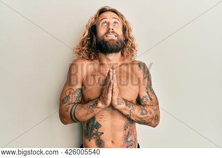 Handsome man with beard and long hair standing shirtless showing tattoos begging and praying with hands together with hope expression on face very emotional and worried. begging.