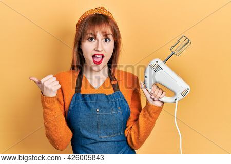 Redhead young woman holding pastry blender electric mixer pointing thumb up to the side smiling happy with open mouth