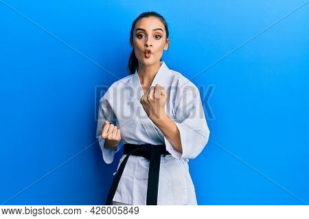 Beautiful brunette young woman wearing karate fighter uniform with black belt doing attack pose making fish face with mouth and squinting eyes, crazy and comical.