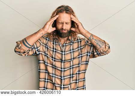Handsome man with beard and long hair wearing casual clothes suffering from headache desperate and stressed because pain and migraine. hands on head.