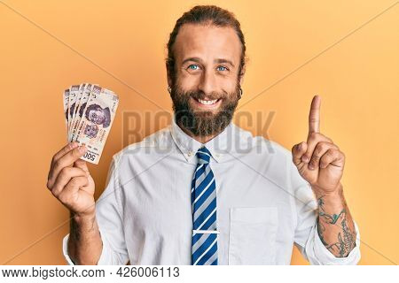 Handsome business man with beard and long hair holding 500 mexican pesos banknotes smiling with an idea or question pointing finger with happy face, number one