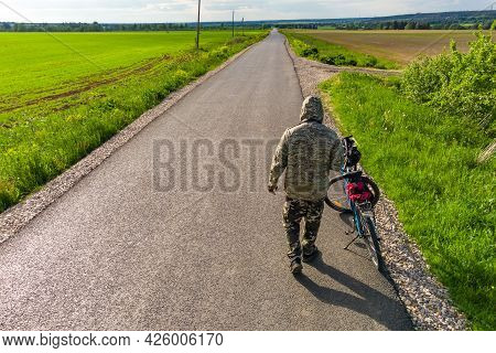 A Cyclist In Camouflage From The Back Next To A Bicycle On The Background Of An Asphalt Road Going I