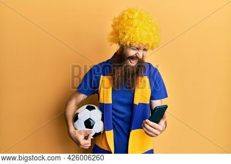 Redhead man with long beard football hooligan cheering game holding smartphone smiling and laughing hard out loud because funny crazy joke.