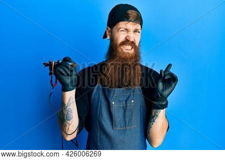 Redhead man with long beard tattoo artist wearing professional uniform and gloves pointing aside worried and nervous with forefinger, concerned and surprised expression