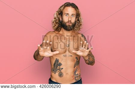 Handsome man with beard and long hair standing shirtless showing tattoos moving away hands palms showing refusal and denial with afraid and disgusting expression. stop and forbidden.