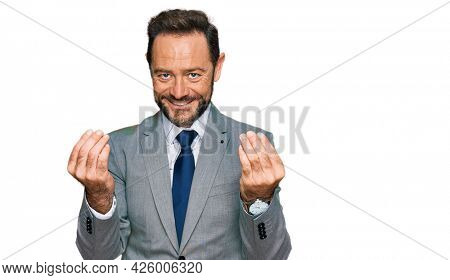 Middle age man wearing business clothes doing money gesture with hands, asking for salary payment, millionaire business