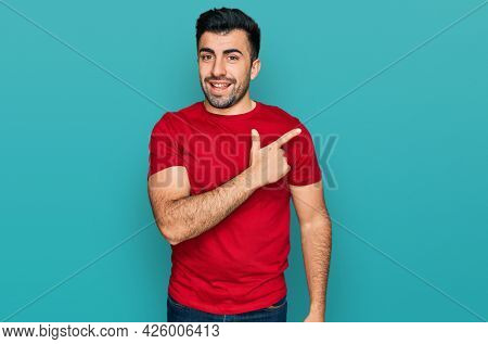 Hispanic man with beard wearing casual red t shirt cheerful with a smile of face pointing with hand and finger up to the side with happy and natural expression on face