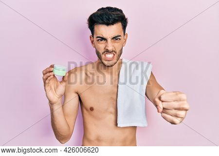 Young hispanic man shirtless wearing towel and eye bags patches annoyed and frustrated shouting with anger, yelling crazy with anger and hand raised