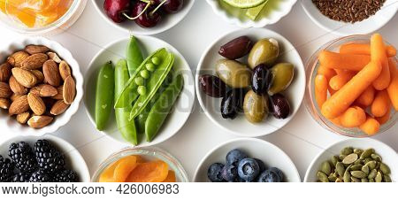 Top Down Close Up View Of Small Dishes Filled With Various Healthy Raw Ingredients, Against A White