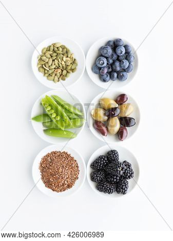 Top Down View Of Small Bowls Filled With Various Healthy Raw Ingredients, Against A White Background