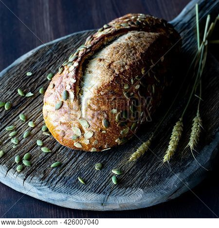 Close Up View Of A Loaf Of Pumpkin Seed Bread On A Rustic Wooden Board Against A Dark Background.
