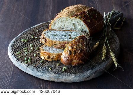 Close Up View Of A Loaf Of Pumpkin Seed Bread Sliced Into On A Wooden Board, Against A Dark Backgrou