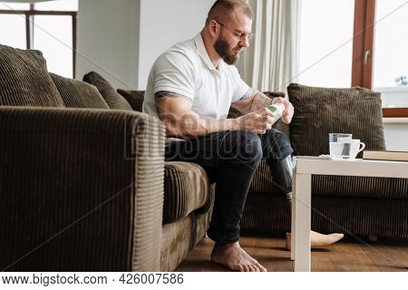 White man with prosthesis taking his medicine while siting on couch at home
