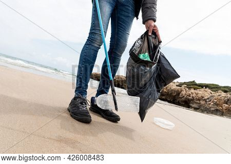 a man collects, with a reach extender, some waste, such as cans, bottles or bags, from the sand of a lonely beach, as an action to clean up the natural environment