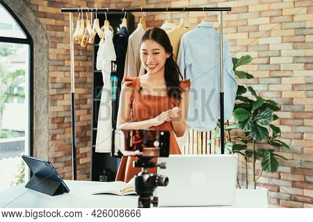 Young And Beautiful Asian Woman Blogger Showing Clothes In Front Of Smartphone Camera While Recordin
