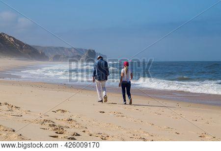 Sao Martinho do Porto, Portugal - July 2, 2021: Couple at the  beach near Sao Martinho do Porto, Portugal