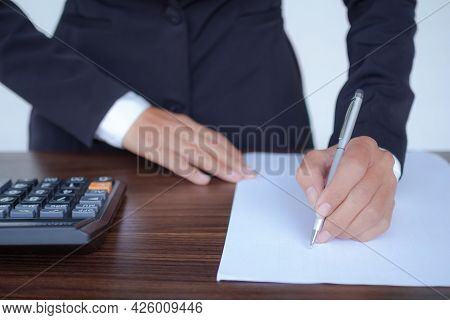Staff Business Woman With Black Suit Holding Pen For Writing On Blank White Document Paper With Calc