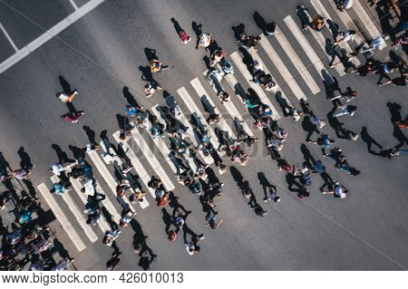Different Blurred People At A Pedestrian Crossing In The City - Drone Shot. People At A Zebra Pedest