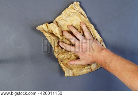 Man Holding A Dirty Brown Paper Bag On A Gray Background. Hand Crumples Paper Bag Which Is Used For