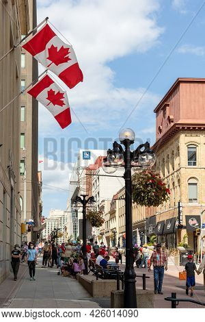 Sparks Street View With Walking People And Canadian Flags On Buildings In Downtown Of Ottawa In Cana