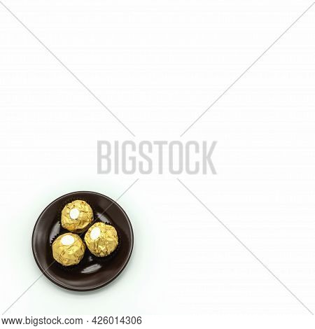 Three Chocolates, Wrapped In Golden Foil, Lie On A Brown Porcelain Saucer. Top View. Lower Left Corn