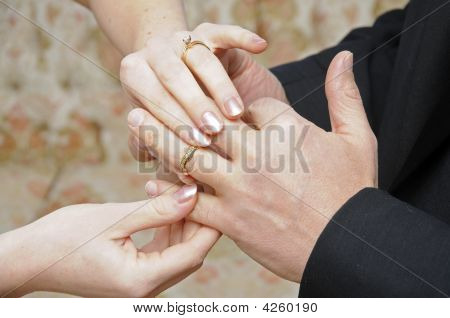 Bride Placing Ring On Finger Of Groom
