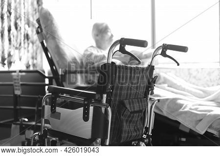 Elderly Woman With Dementia Playing With Towelettes While Relaxing In A Nursing Bed