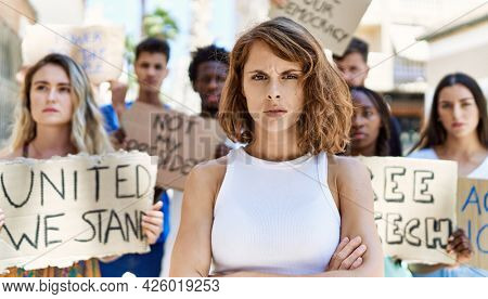 Young activist woman with arms crossed gesture standing with a group of protesters holding banner protesting at the city.