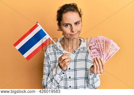 Young brunette woman holding thailand flag and baht banknotes skeptic and nervous, frowning upset because of problem. negative person.