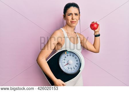 Young hispanic woman wearing sportswear holding weighing machine and apple clueless and confused expression. doubt concept.