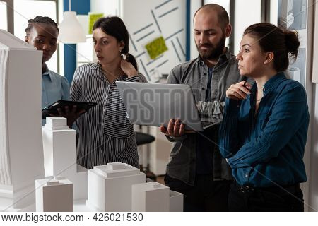 Architecture Multi Ethnic Workers Meeting At Office Analyzing Blueprint Plans On Laptop Computer Tab