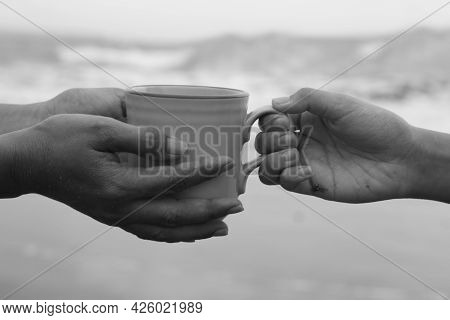 Hands Of Two People Holding A Cup Of Coffee Or Tea On Beach In Black And White Abstract Art Backgrou